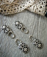 Pair of dirndl hooks - closed loop style.  Silver tone with stylized flower design.